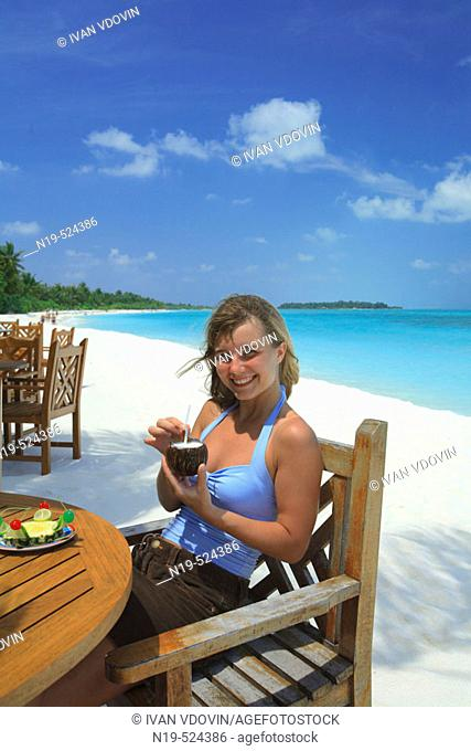 Portrait of young woman on the beach with cocktail, Maldives, Indian ocean