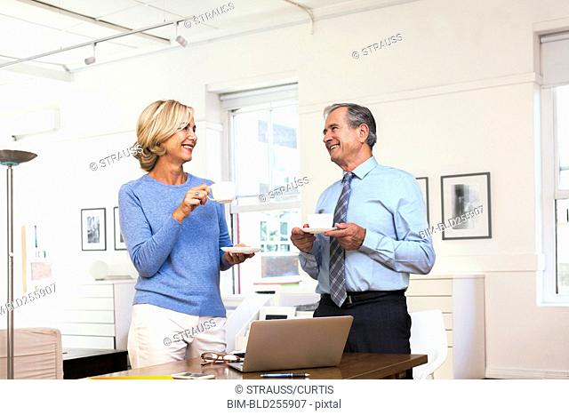 Caucasian businessman and businesswoman drinking coffee
