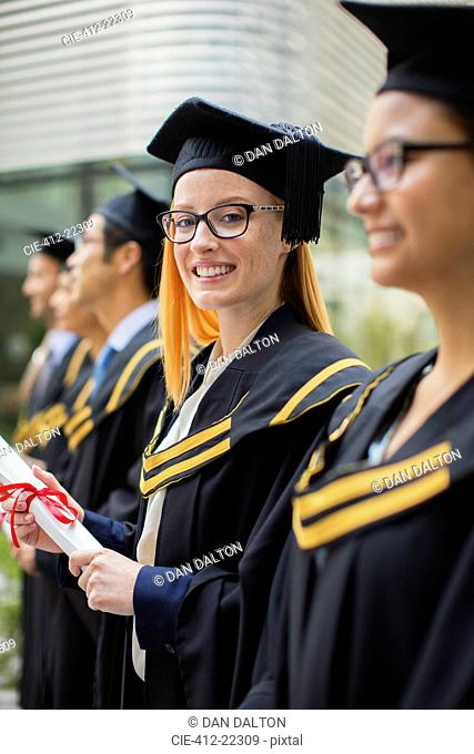 Woman in cap and gown standing with colleges