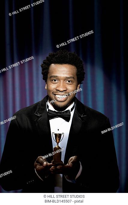 Smiling Black man in tuxedo holding tiny award trophy