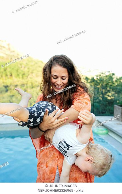 Woman playing with son at swimming-pool