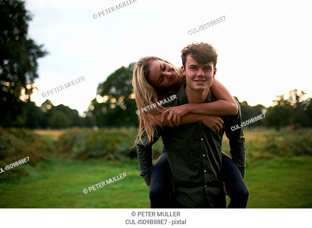 Young man giving girlfriend a piggyback in field