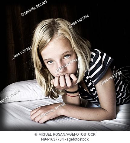 Blonde teen lying face down on the bed