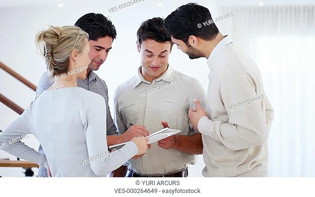 Four young businesspeople making notes on a document while having a discussion
