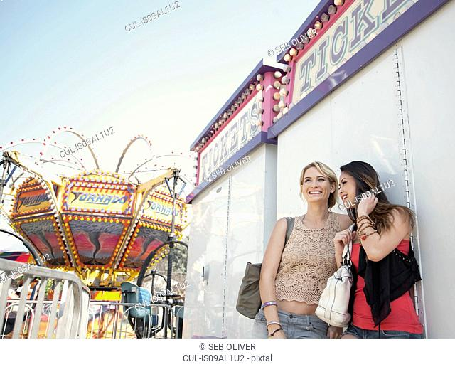 Two women at fairground, smiling and watching surroundings