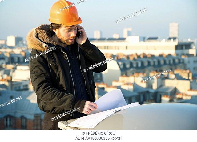 Construction supervisor studying blueprints and talking on cell phone