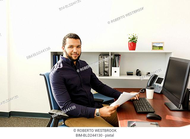 Mixed Race man reading paperwork near computer in office