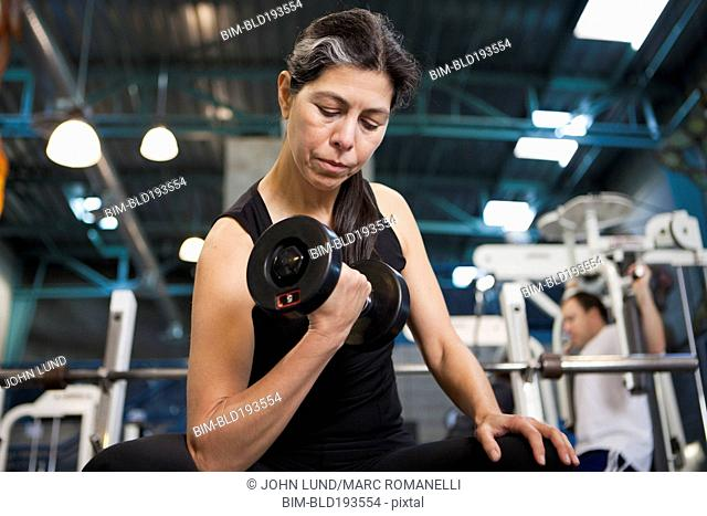 Hispanic woman lifting weights
