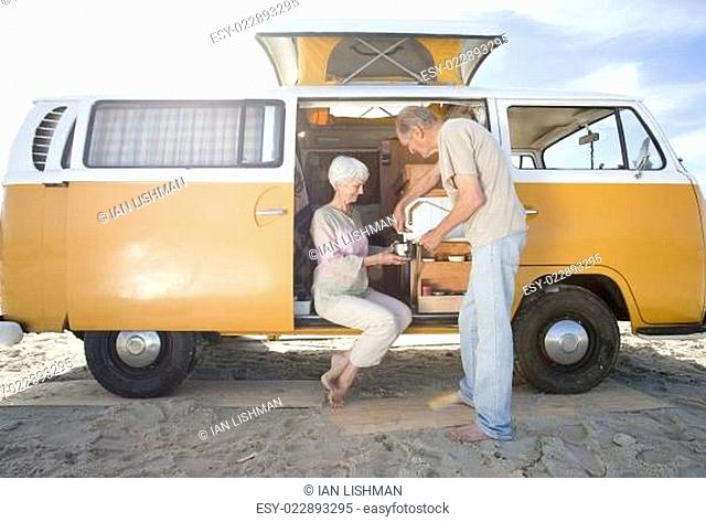 Senior couple making tea in camper van on beach