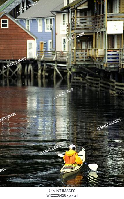 A man in a kayak in the creek by the jetty in Ketchikan