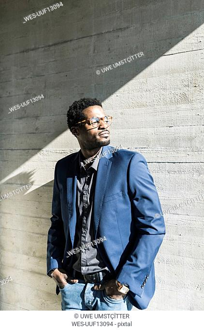 Businessman standing in sunshine at concrete wall looking away