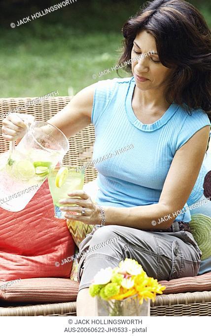 Mature woman pouring lemonade into a glass
