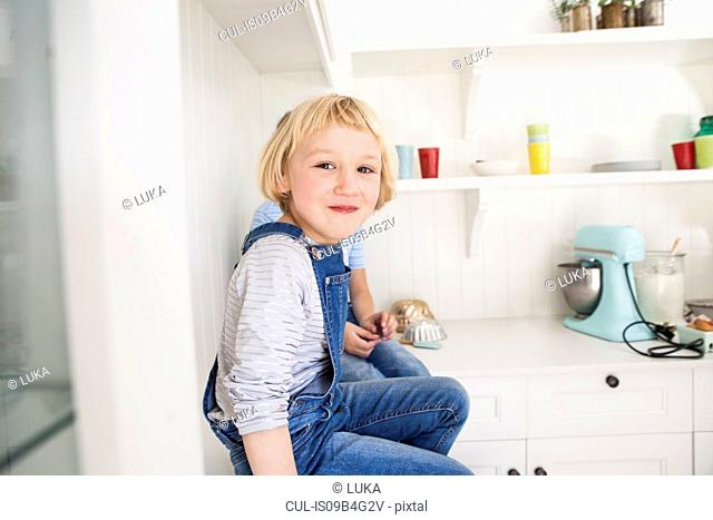 Portrait of cute girl sitting in front of brother on kitchen counter