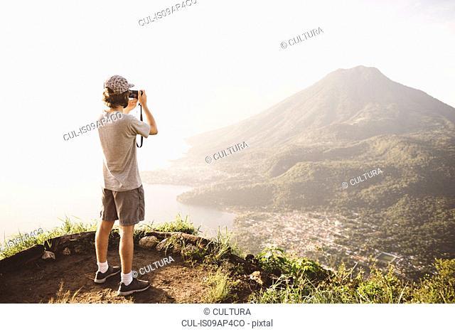 Young man photographing at Lake Atitlan on digital camera, Guatemala