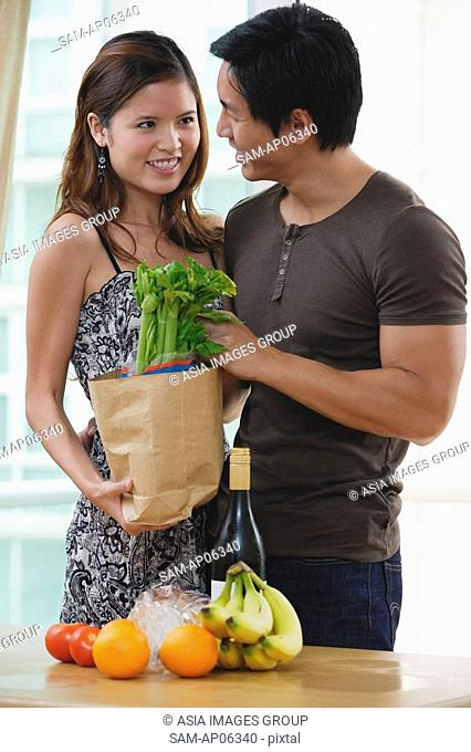 Couple smiling at each other, woman holding shopping bag with groceries