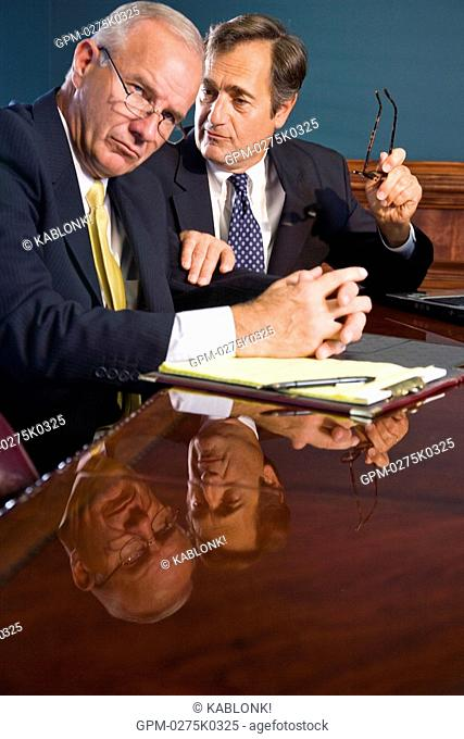 Two corporate executives in conference room with serious expression