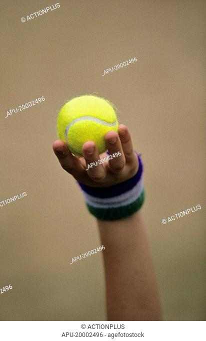 Ball boy holding up a tennis ball
