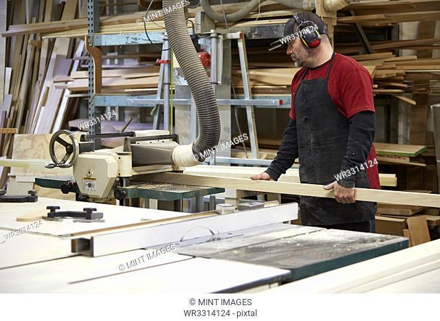 Carpenter using saw in workshop