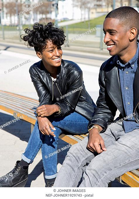 Smiling young couple sitting on bench