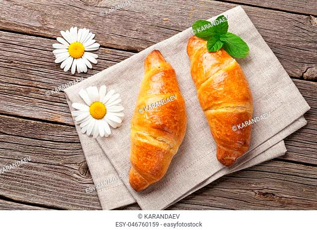Croissants and chamomile flowers on wooden table. Top view. Breakfast concept