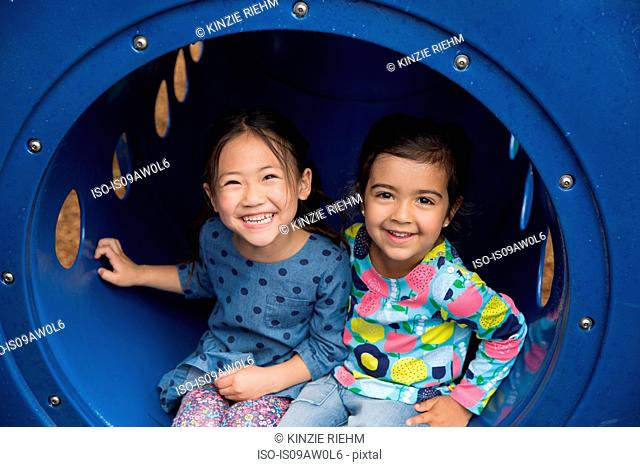Portrait of two girls sitting in playground tunnel