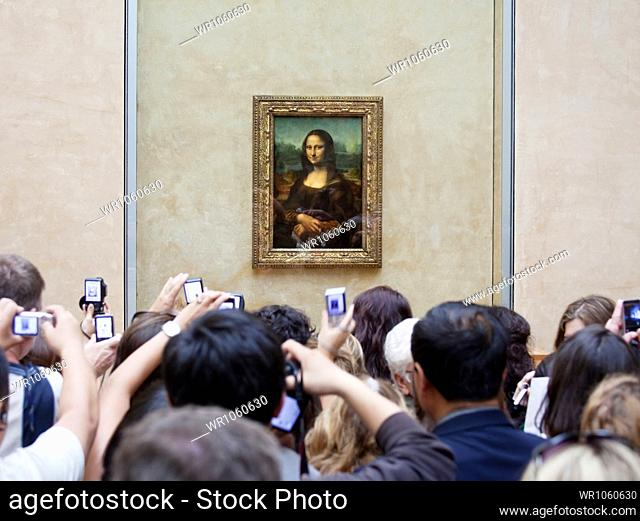 France, Paris, Tourists photographing Mona Lisa painting