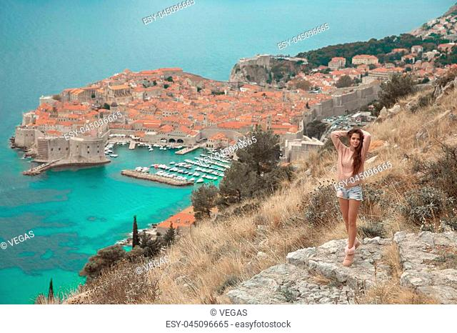 Brunette Girl tourist visiting mountain viewpoint sightseeing in Dubrovnik, Croatia. Woman traveller in front on famous travel destination