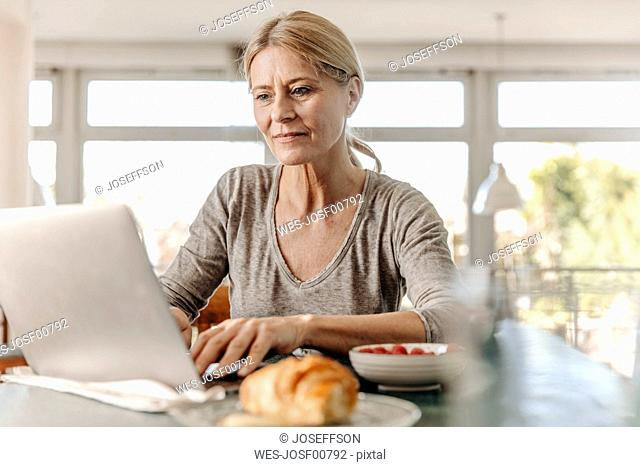 Woman at home having breakfast and using laptop