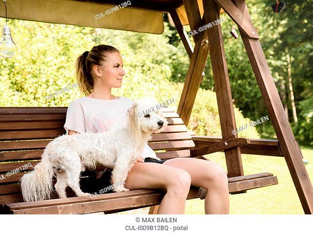 Woman sitting on swingchair with coton de tulear dog, Orivesi, Finland