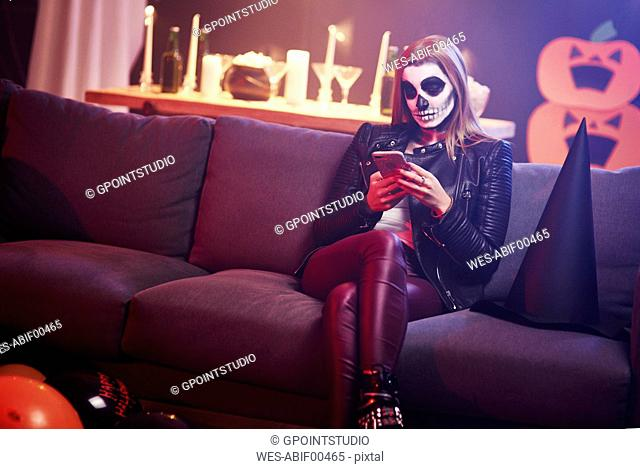 Bored woman using mobile phone at Halloween party