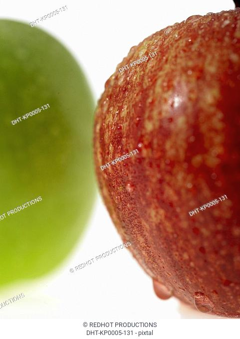One green apple and one red apple with dew on them