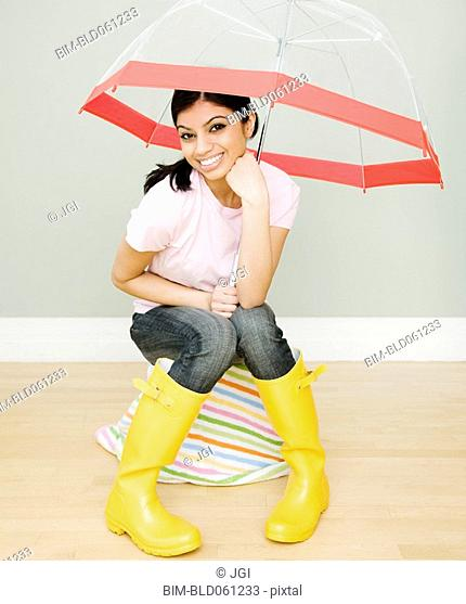 Mixed Race woman with umbrella and rain boots