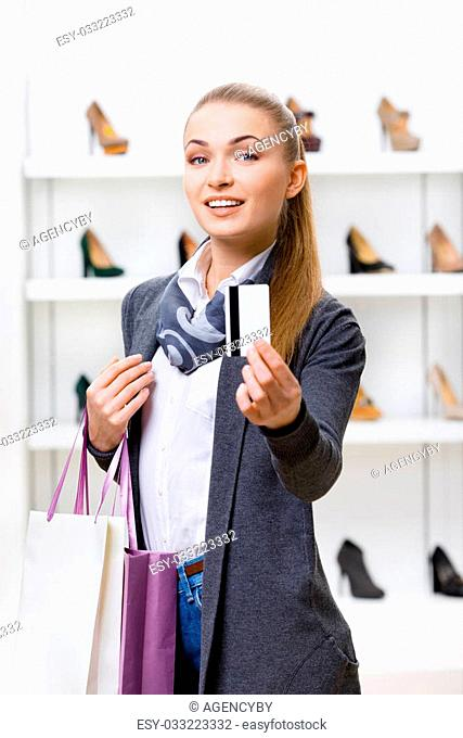 Lady showing credit card in footwear shop with great variety of stylish shoes