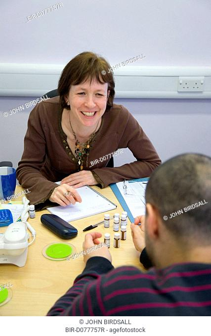 Homeopathic consultant discussing treatments with a patient
