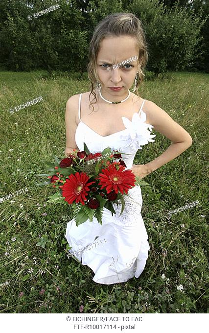 Bride with hand on hip outdoors, portrait