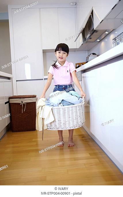 Girl Looking At Clothes In Laundry Basket