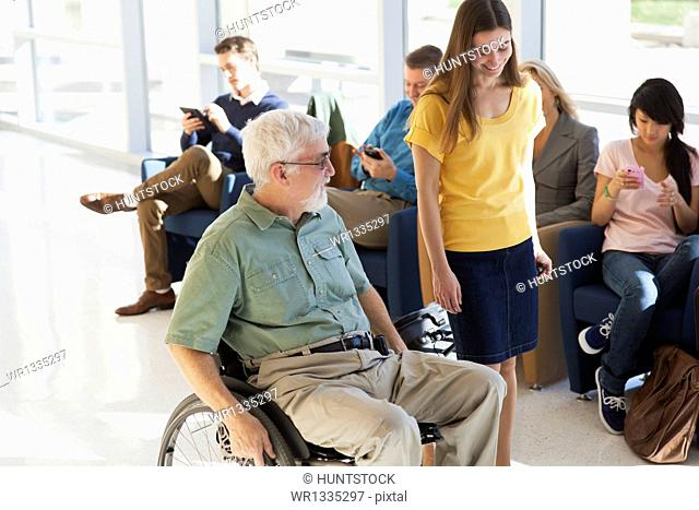 Man with Muscular Dystrophy in a wheelchair walking with another passenger in a corridor of an airport