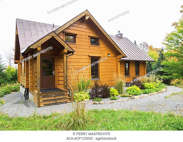 Piece sur piece Scots pine log home facade with brown standing seam sheet metal roof in autumn, Quebec, Canada. This image is property released