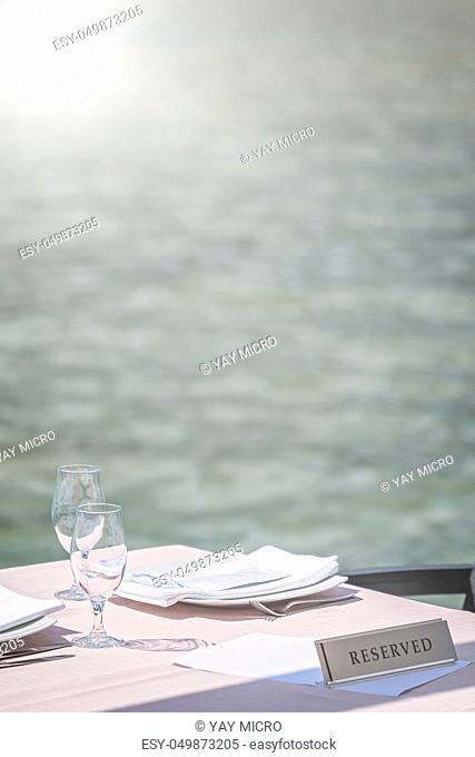 Empty glasses on a reserved outdoor restaurant table at a seaside resort