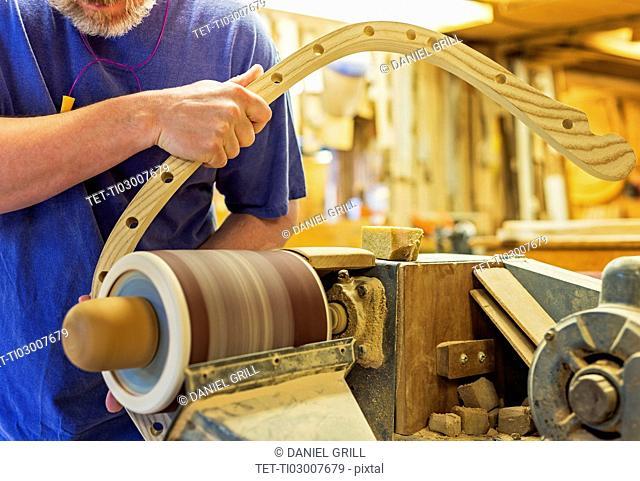 Carpenter polishing wood with sander