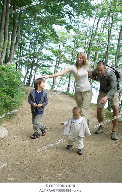 Parents playing with children in woods