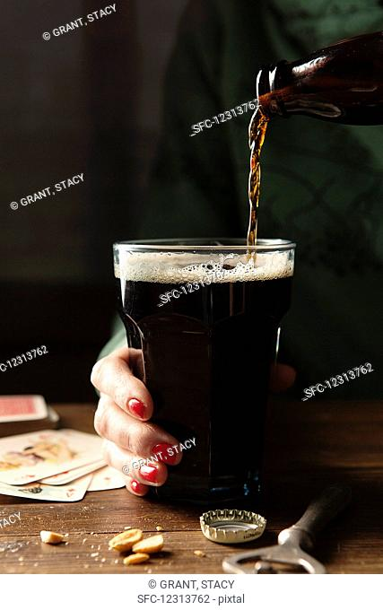 Bottle of Guinness being poured into a large glass being held by a hand with red nail varnish on a wooden table surrounds by the bottle top, bottle opener