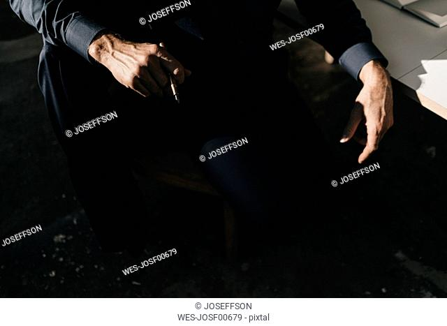 Businessman holding pencil in office