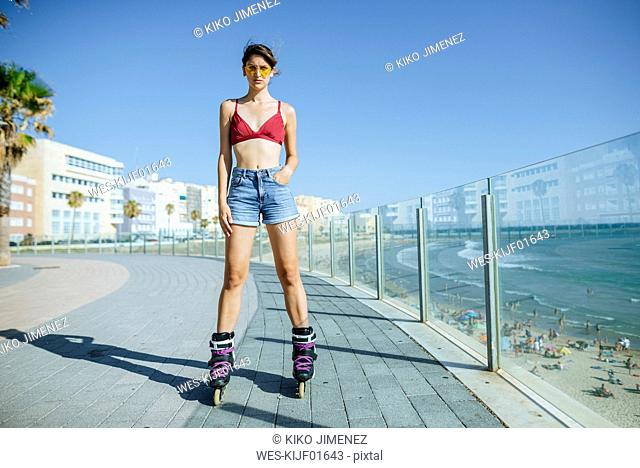 Young woman on inline skates on boardwalk at the coast