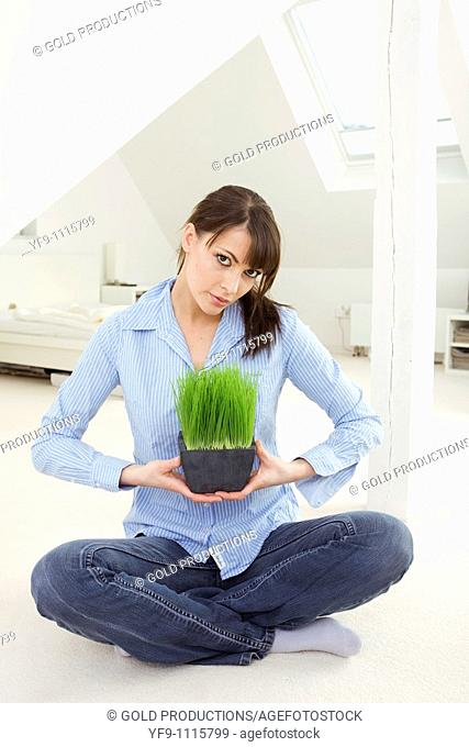 Young woman holding a pot plant
