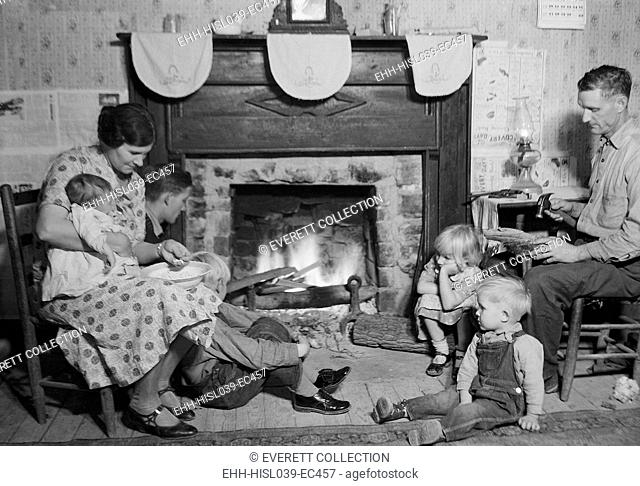 Fletcher Carden is a night-watchman at the bunkhouses at TVA's Norris Dam. He repairs a shoe while sitting by the fireplace with his wife and family