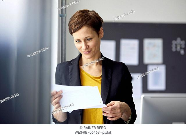 Attractive businesswoman standing in office, readiing document