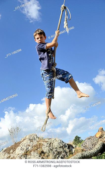 Nine year old boy launching from a tree on a rope swing Atiamuri, New Zealand