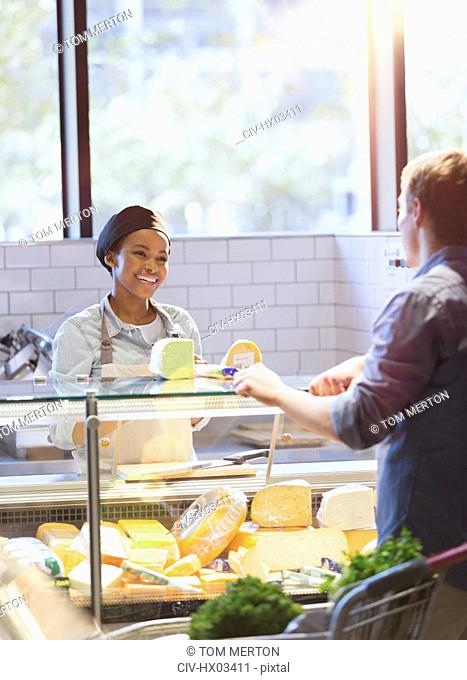 Smiling young woman helping customer at cheese counter in grocery store market