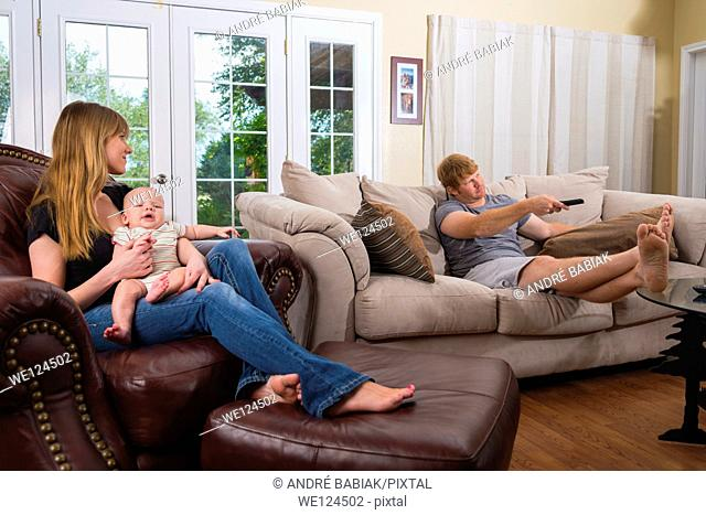 Young Parents - Mother taking care of baby while father is watching TV